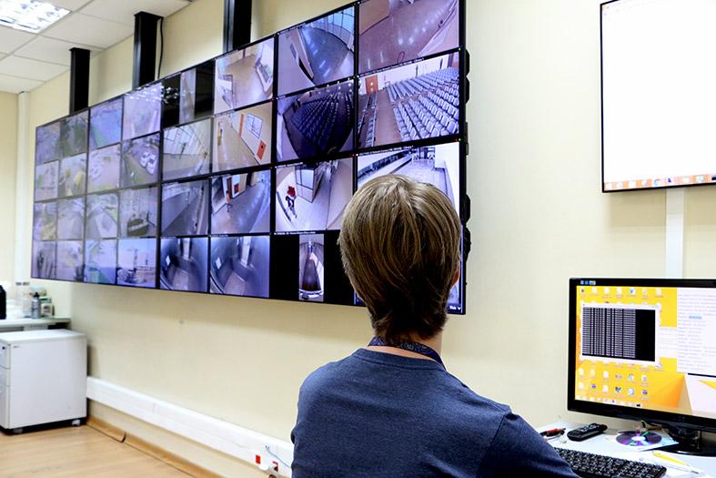 Servidor da assessoria de segurança institucional monitora a segurança da sede do tribunal de justiça através de uma parede com televisores.