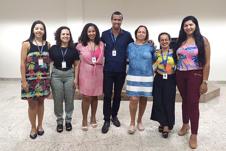 6 mulheres e 1 homem posam de pé para foto