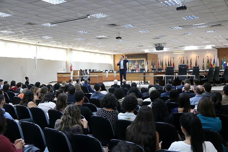 Auditório (Salão do Pleno) cheio de pessoas assistindo a um homem de terno falar de pé ao microfone.
