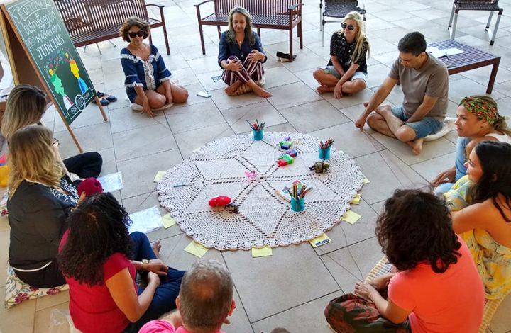 Pessoas sentadas em círculo no chão, no cetro da roda uma toalha em crochê e vários elementos coloridos em cima.