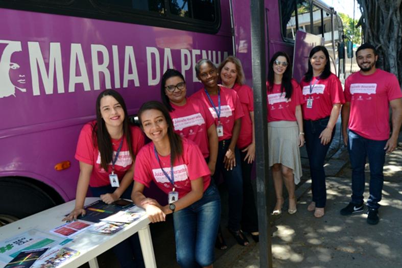 Voluntários posam em frente a ônibus de cor rosada.