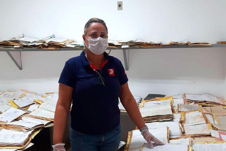 Colaboradora da empresa de restauração de processos posa para foto em uma sala cheia de processos. Ela usa camisa azul marinho, calça jeans, máscara de proteção no rosto e touca higiênica na cabeça.