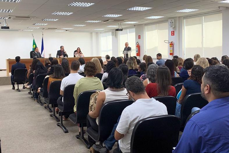 EM um auditório lotado pessoas assistem a palestra de duas pessoas.
