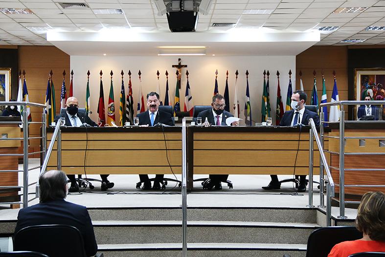 Quatro homens sentado em mesa de honra durante um evento no salão pleno do TJES