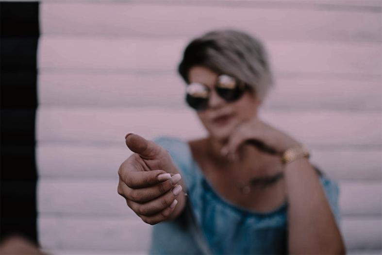 imagem em tom rosado de uma mulher fazendo o sinal de positivo com a mão.