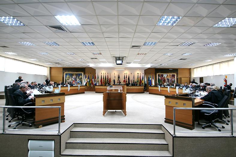 Foto panorâmica do salão pleno do tribunal de justiça onde se vê 30 assentos e ao fundo baneidras dos estados e dois quadros bem coloridos.