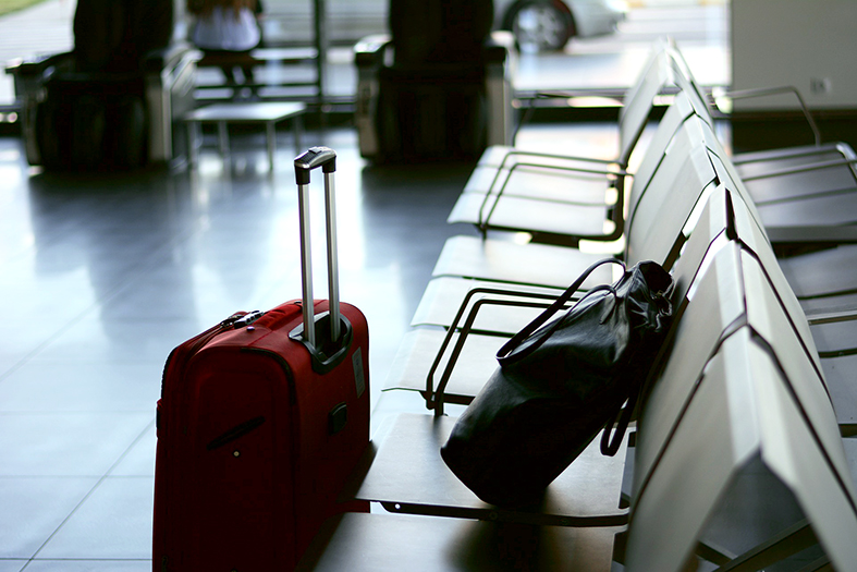 Uma mala vermelha pequena e uma pasta preta repousam em cadeiras de um saguão de embarque de um aeroporto.