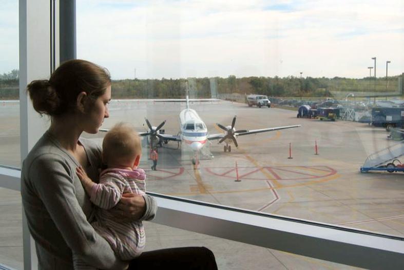 Mãe e bebe de colo observam os aviões em aeroporto.