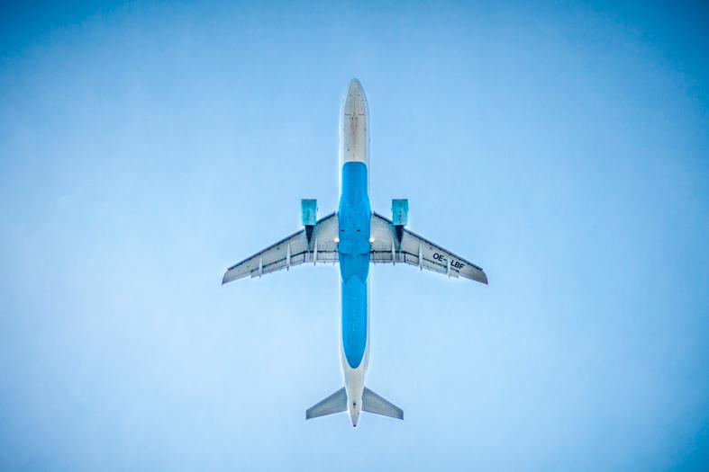 Vista inferior de um avião cruzando um céu azul.