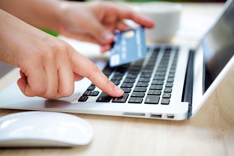 Mãos segurando um cartão de crédito e digitando em um teclado de um laptop