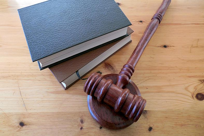 Um gavel (martelinho) de juiz repousa sobre sua base, ao lado dele estão dois livros sobrepostos.