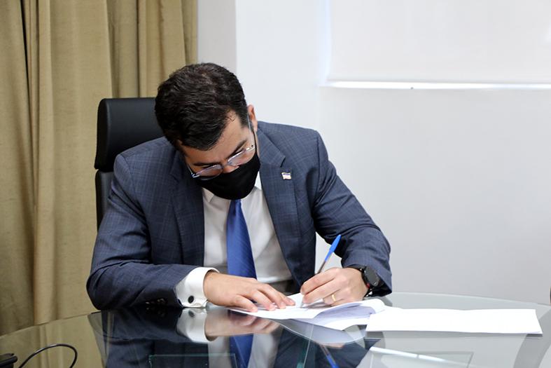 O Procurador-Geral do Estado, Jasson Amaral Hibner, assinando um documento.