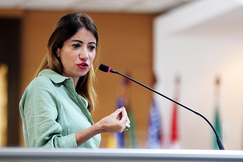 A uíza do TJRJ Adriana Ramos de Melo, uma mulher de pele branca e de cabelos pretos com mechas loiras fala ao microfone.