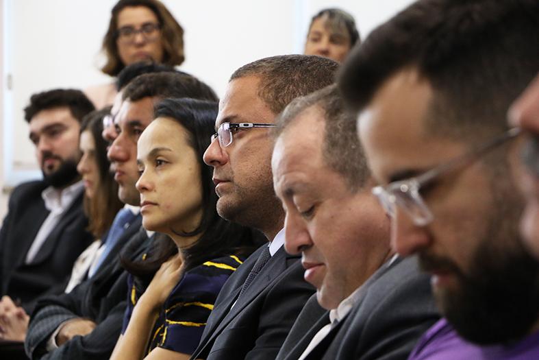 Close em vários rostos de homens e mulheres assistindo a uma audiência