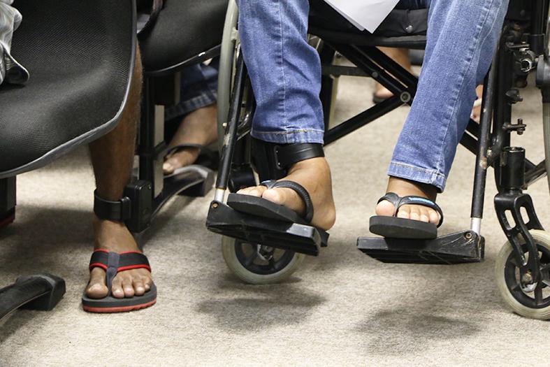 Pés de uma pessoa usando calça jeans e uma tornozeleira eletrônica em sua canela esquerda