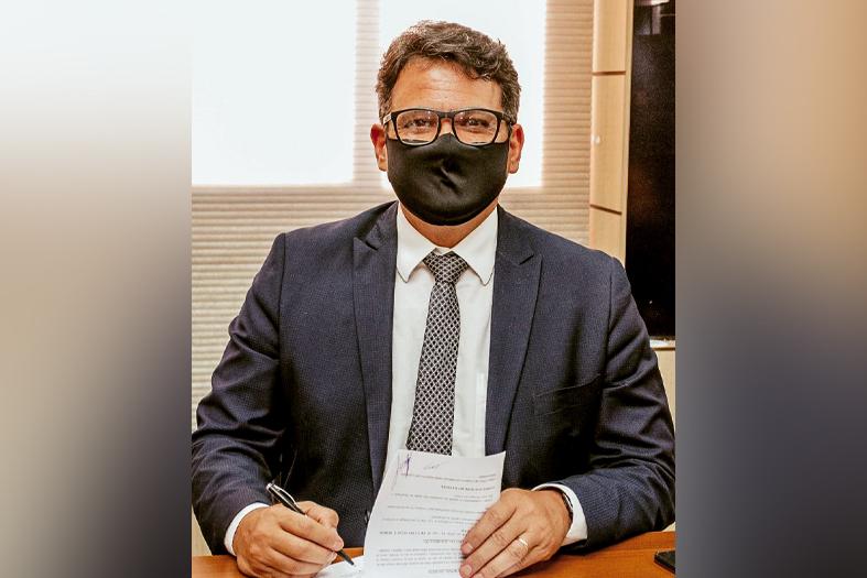 Carlos Eduardo, juiz da 7ª Vara Criminal de Vitória, assina convênio. Ele é um homem de pele morena, tem cabelos castanhos e usa óculos.