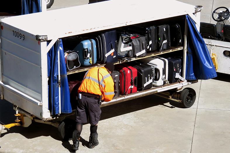 Funcionário de aeroporto transportando malas.