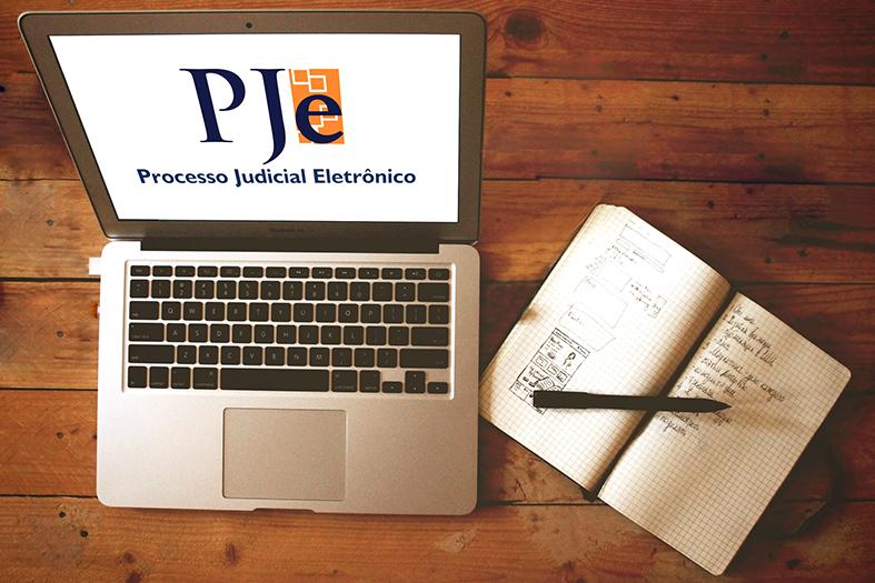 Visão de cima de uma mesa de madeira onde repousa um laptop com a tela aberta projetando a marca do PJe (Processo Judicila Eletrô