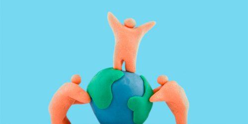 3 figuras em massa de modelar interagem com um globo terrestre feito do mesmo material.