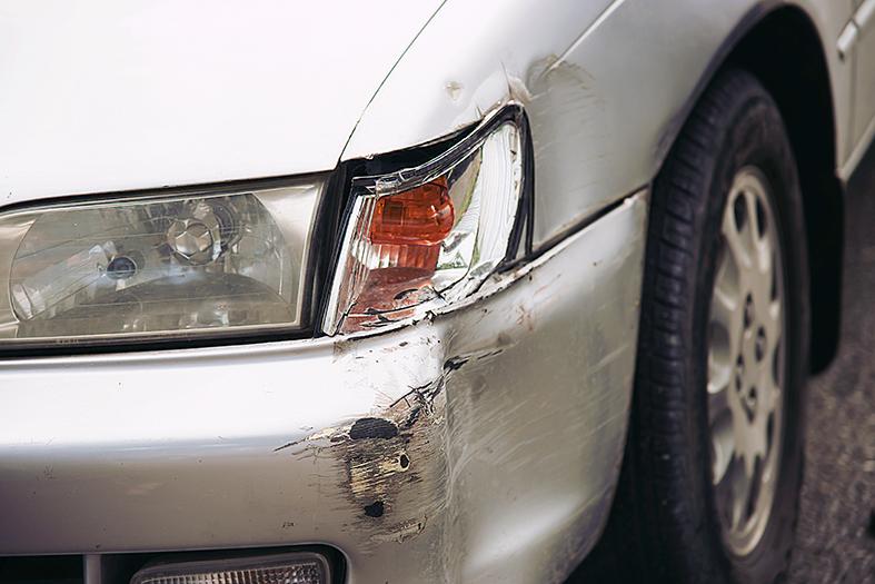 Detalhe de um para choque amassado de carro na cor prata