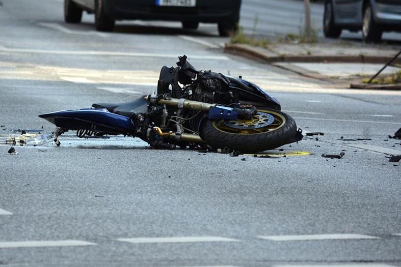 motocicleta avariada jogada no asfalto.
