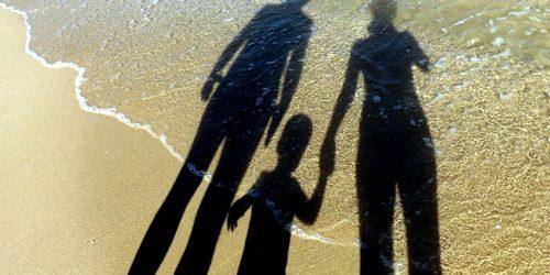 Silhueta de uma família projetada na areia.
