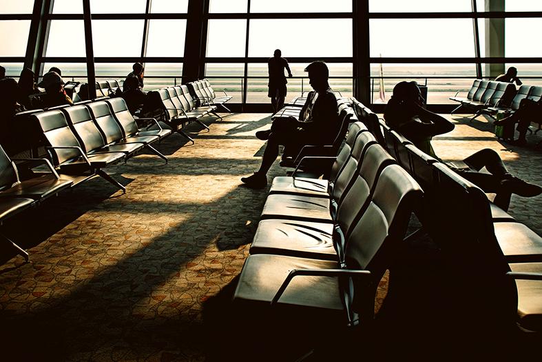Silhueta de pessoas em saguão de aeroporto.