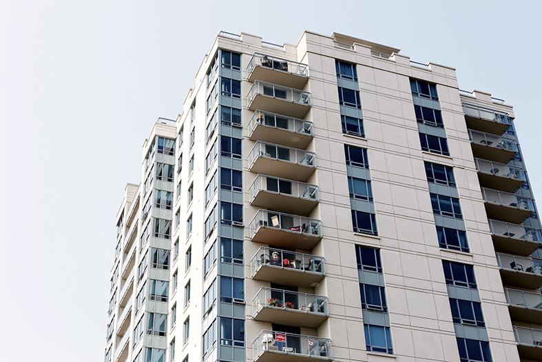 Prédio de apartamentos coma fachada nas cores branca e azul.