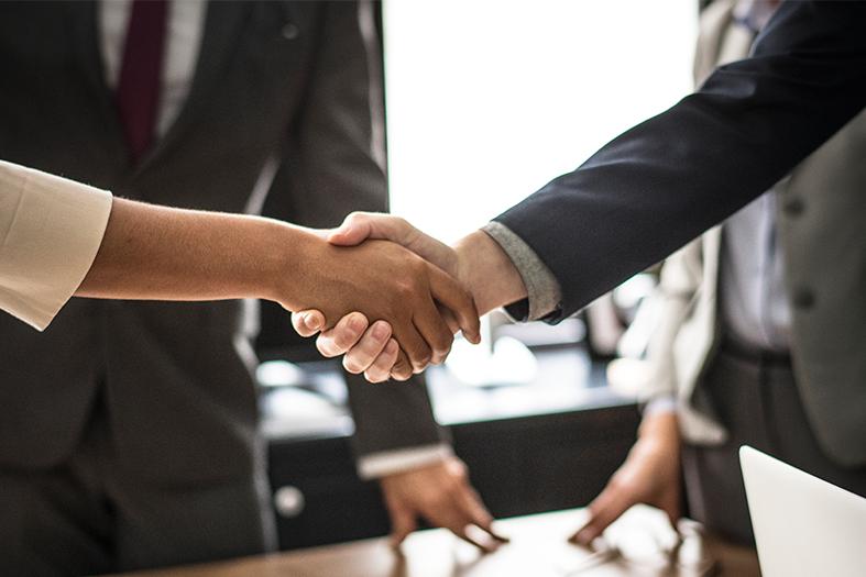 Em um escritório, um homem de terno aperta a mão de uma mulher.