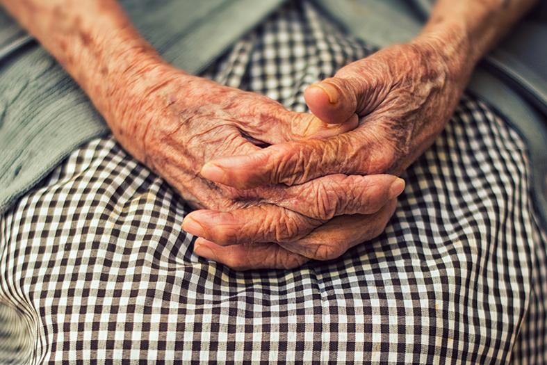 Mãos de uma idosa cruzadas sobre seu colo