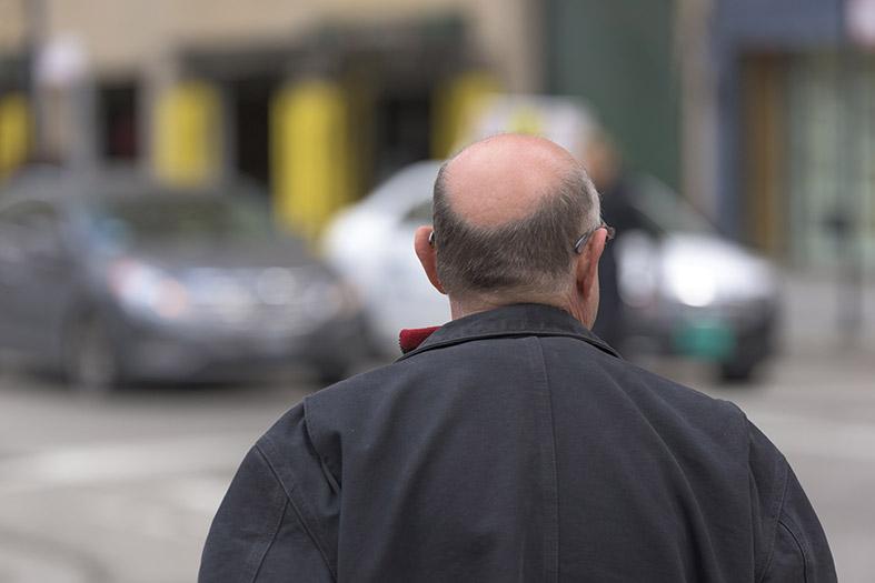 Visão das costas de um idoso calvo andando na rua.