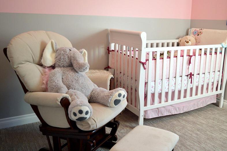 Quarto de recém nascido com decoração em tons da cor rosa, no berço vemos um urso de pelúcia bege e na cadeira de balanço um elefante de pelúcia na cor cinza claro.