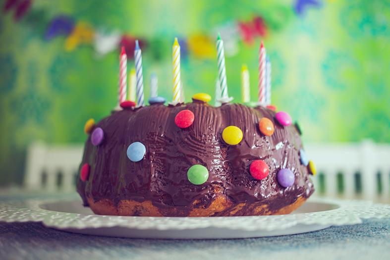 Bolo decorado com calda de chocolate e confetes mastigáveis coloridos.