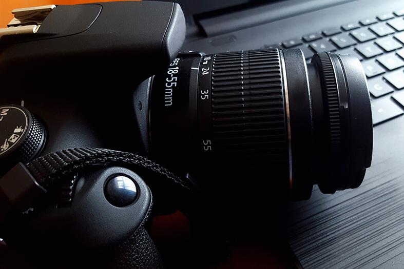 Câmera fotográfica profissional de cor preta sobre um teclado de laptop.