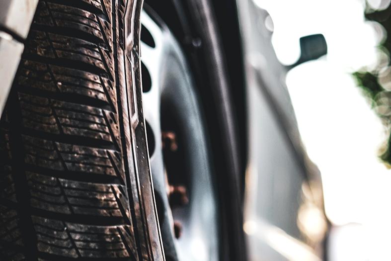 detalhe de uma roda traseira de um carro. a imagem tem a perspectiva a partir da roda traseira do carro e o resto dele está fora de foco.