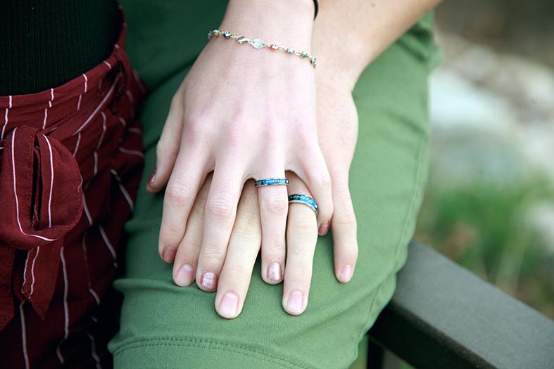 Mãos de um casal de namorados entrelaçadas.