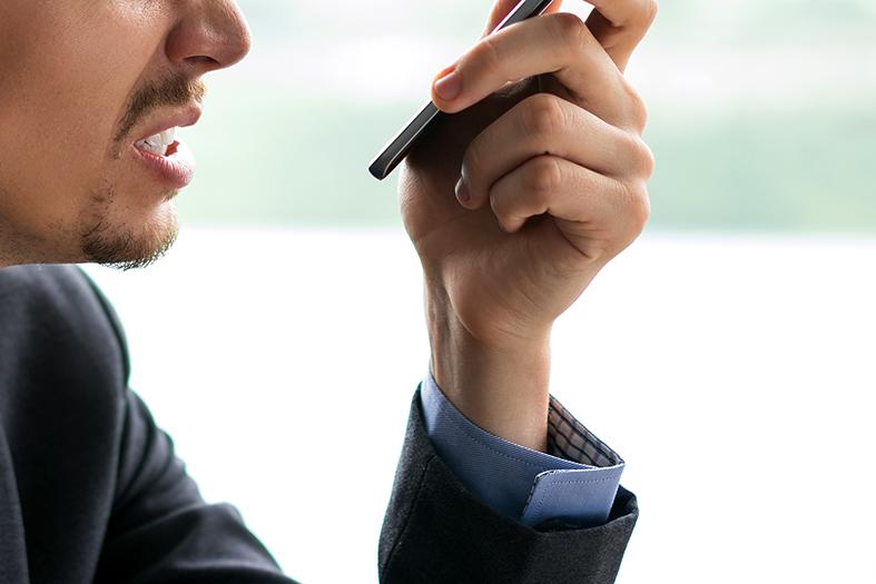 Detalhe de um homem com expressão de raiva e um smartphone na mão.