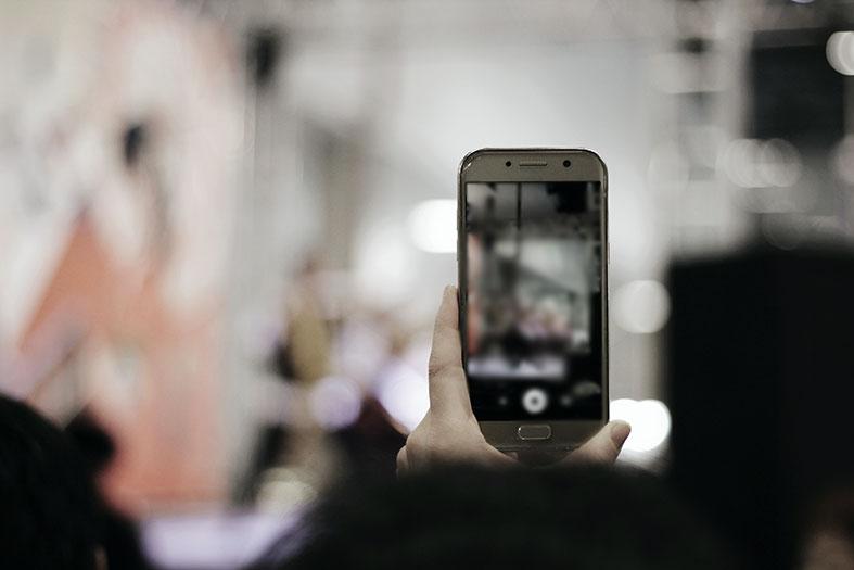 Mão de pessoa filmando com o celular.