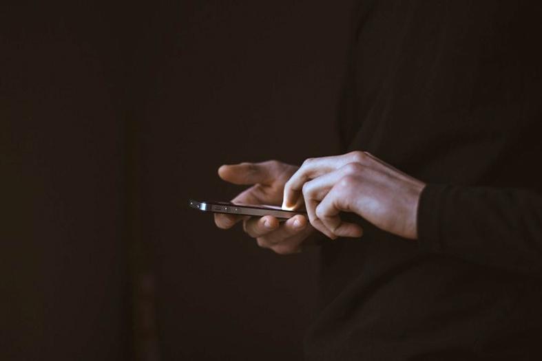 ambiente escuro ou com pouca luz. em destaque mãos masculinas operando um celular smartphone
