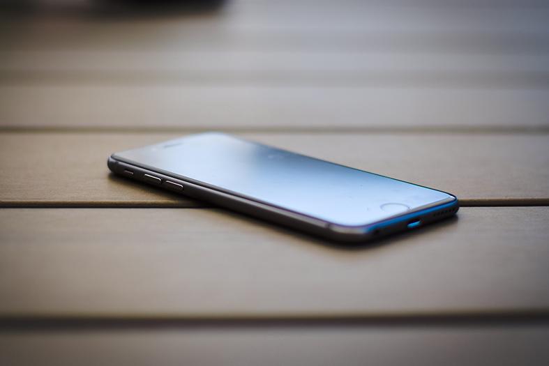 Celular modelo smartphone repousa sobre uma mesa de madeira.