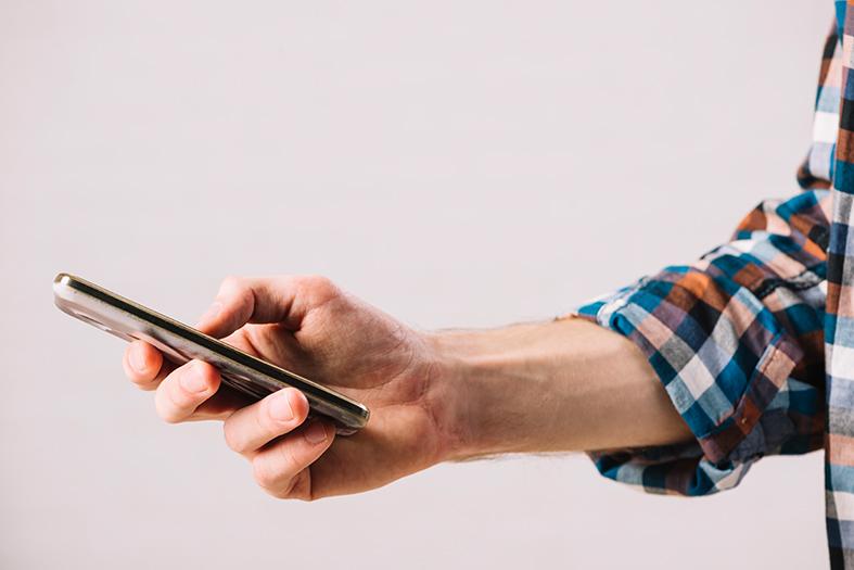 Mão de um homem segura um celular do tipo smartphone.
