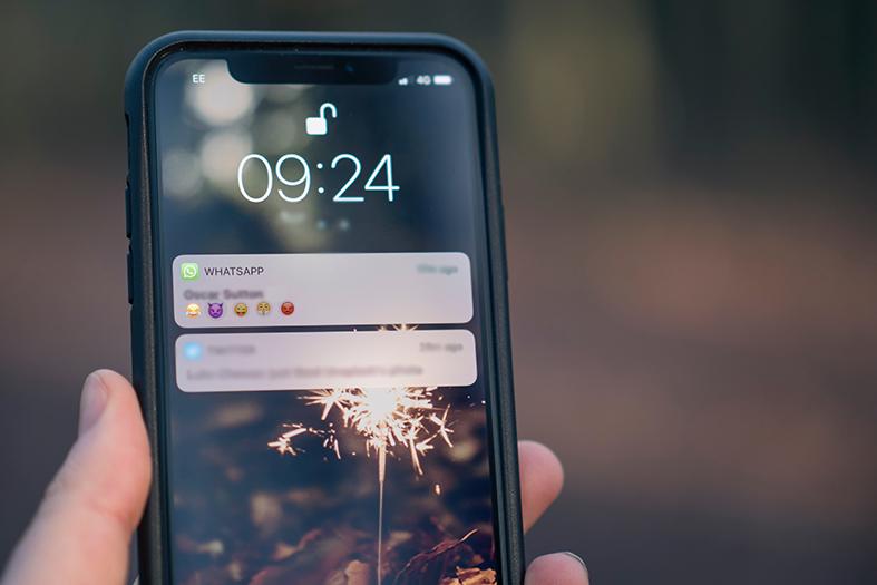 Detalhe de mãi de home segurando um celular cuja tela mostra uma notificação de whastapp.