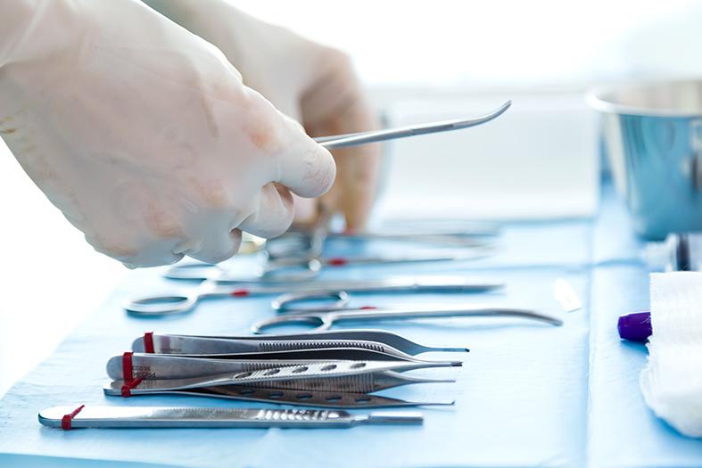Detalhe de instrumentos de cirurgia sendo manipulados por mãos com luvas.