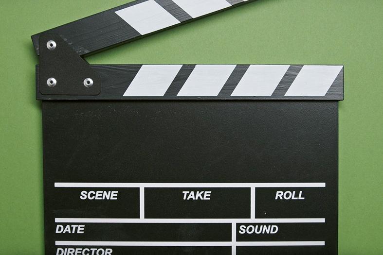 claquete de cinema na cor preta sobre fundo na cor verde.