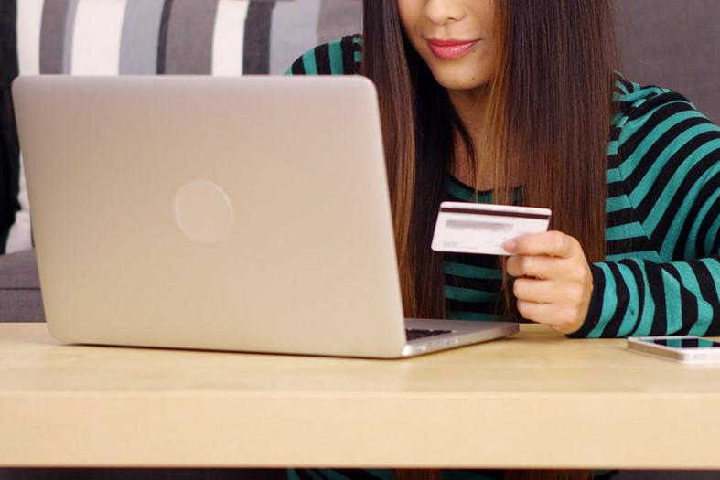 Mulher de pele branca e de cabelos na cor marrom escura segura cartão de crédito em frente a um notebook.