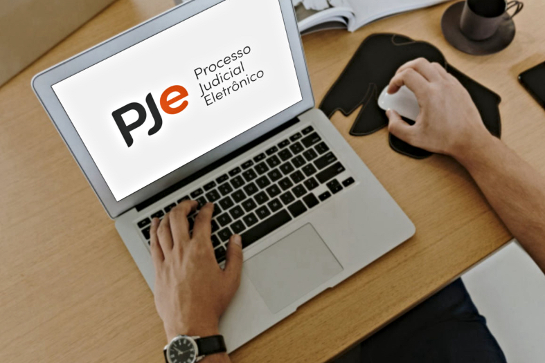 """Fotografia dos braços de uma pessoa utilizando um laptop. Na tela, sobre um fundo branco, está projetado o logotipo do Pje e ao lado dele o texto """"Processo Judicial Eletrônico""""."""