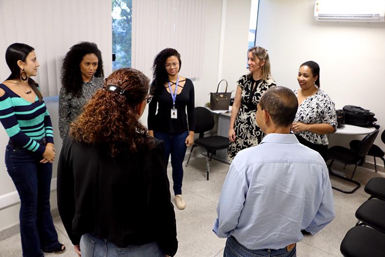 Grupo de 6 mulheres e um homem de pé em círculo.
