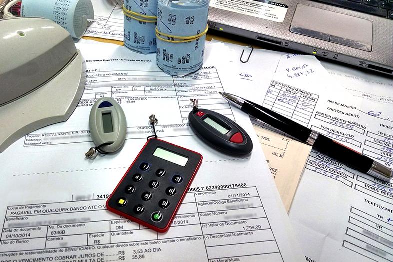 Pilha de contas, boletos bancários e calculadora.
