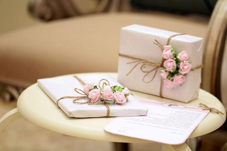 convites de casamento decorados com rosas e fitas douradas.