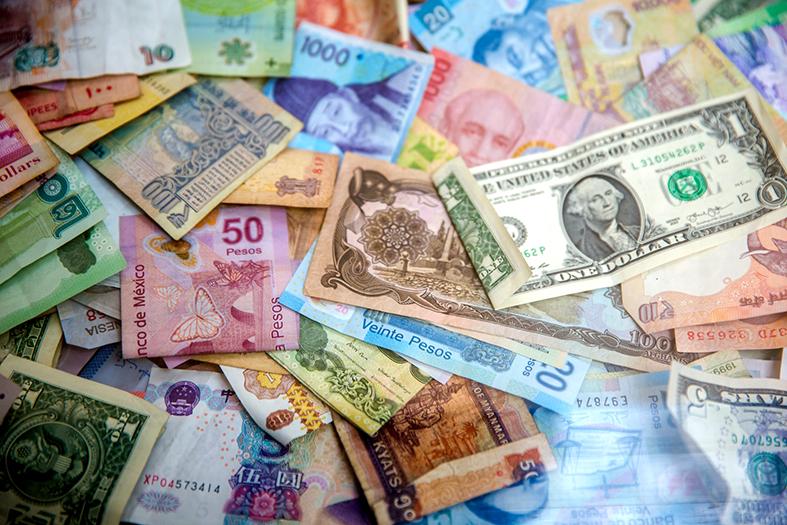 vários tipos de papel-moeda espalhados.